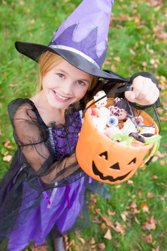 Girl in purple halloween costume holding up a bucket of candy
