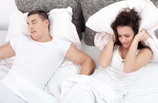 Woman covering her ears with pillow while man snores